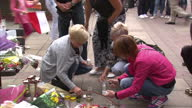 Shows exterior shots people at memorial for Arkadiusz Jozwik Polish man killed in possible hate crime attack laying flowers lighting candles holding...