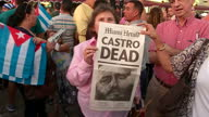 Shows exterior shots people celebrating Fidel Castro's death in Little Miami Florida USA with crowds holding papers announcing his death and waving...