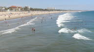 Shows exterior shots people enjoying themselves on Santa Monica Beach and playing in the surf on 26th July 2017 in California USA