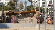 Shows exterior shots people exercising and swinging on rings on Santa Monica Beach on 26th July 2017 in California USA