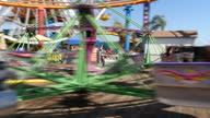 Shows exterior shots people having fun on spinning amusement park ride at Pacific Park at Santa Monica Beach on 26th July 2017 in California USA