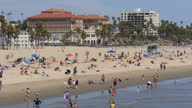 Shows exterior shots people on the beach and in the sea at Santa Monica Beach on 26th July 2017 in California USA