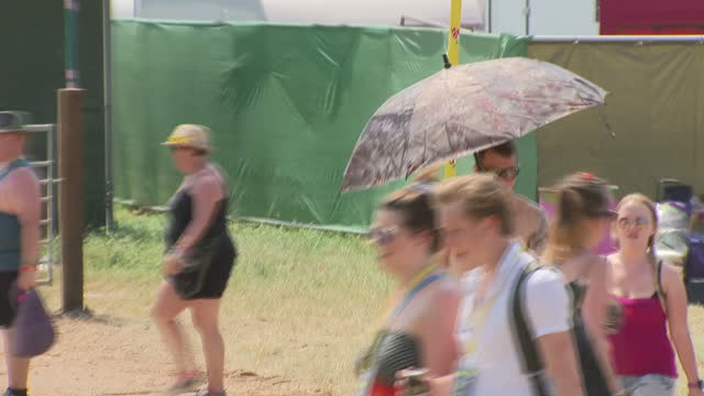 Shows exterior shots people using umbrellas to shelter from the sun and carrying blow up mattress through campsite at Glastonbury Festival on 22nd...