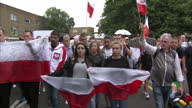 Shows exterior shots people walking in silence holding Polish flags at march to commemorate a Polish man killed in a possible hate crime attack in...