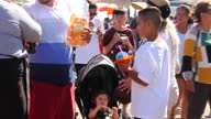 Shows exterior shots people walking on Santa Monica pier eating junk food and ice drinks on 26th July 2017 in California USA