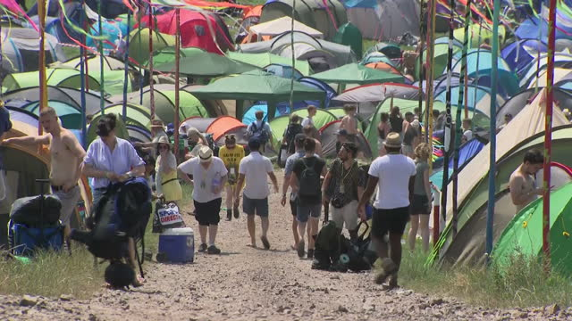 Shows exterior shots people walking with bags and supplies through campsite at Glastonbury Festival on 22nd June 2017 in Glastonbury Somerset England
