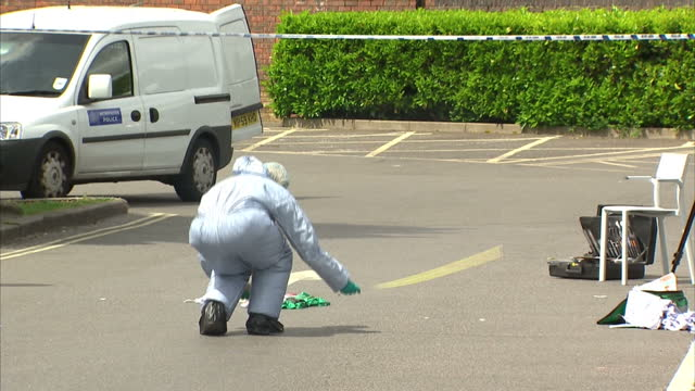 Shows exterior shots police forensics officers writing notes and taking measurements at crime scene Exterior shots evidence at crime scene and police...