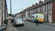 Shows exterior shots police officers standing in road behind cordon tape and talking to residents at housing estate where suspect was arrested Two...