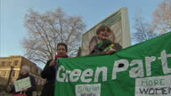 Shows exterior shots press gathered for Green Party announcement party members demonstrating with banners on College Green with one woman with a...