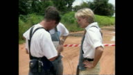 Shows exterior shots Princess Diana laughing with charity workers as they prepare a detonator and pressing button to detonate landmine in cordoned...