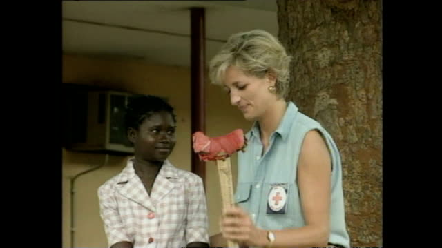 Shows exterior shots Princess Diana sitting with victims of landmines with missing limbs during her Red Cross visit to Angola for campaign against...