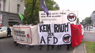 Shows exterior shots protesters marching through streets with banners and flags proetsting against far right groups including AFD German chancellor...