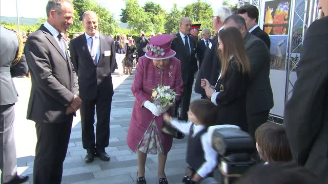 Shows exterior shots Queen Elizabeth II being presented with gifts including model boat and posy of flowers The Queen opens a new section of the...