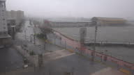 Shows exterior shots through hotel window strong winds whipping rain and blowing trees and debris around as Hurricane Maria hits bay and shoreline in...