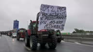 Shows exterior shots Tractors trucks and protesters moving slowly along motorway creating a blockade as they demand the closure of the Calais Jungle...