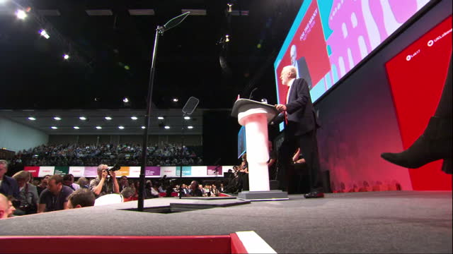Shows exterior shots UK Labour Party Leader Jeremy Corbyn arriving at Labour Party Conference venue shaking hands with people waiting outside walking...