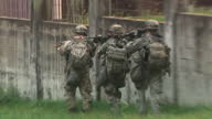 Shows exterior shots US soldiers running between buildings and along perimeter wall in an urban environment during training exercise It's leader has...