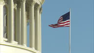 Shows exterior shots various American flags blowing in breeze outside the United States Capitol Building on February 01 2017 in Washington DC