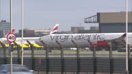 Shows Exterior shots Virgin Atlantic plane taxiing to start of runway with British Airways plane taking off at Heathrow Airport on February 15 2016...