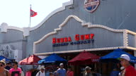 Shows exterior shtos Bubba Gump Shrimp Company shop on Santa Monica Pier and people walking past and queuing outside on 26th July 2017 in California...