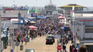 Shows exterior shtos crowds of people filling pier looking at shops and amusements and people making way to and from the beach in cars and on foot on...