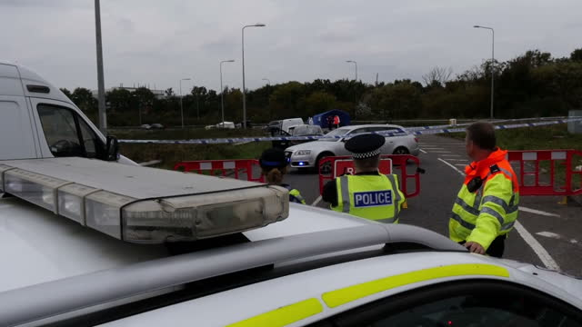 Shows exterior shtos police and forensics officers on cordoned off road at site of police shooting A man has died following a police shooting in...