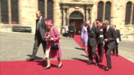Shows exterior shtos Queen Elizabeth II and Prince Philip Duke of Edinburgh walking with officials from chapel into Stirling Castle The Queen and...