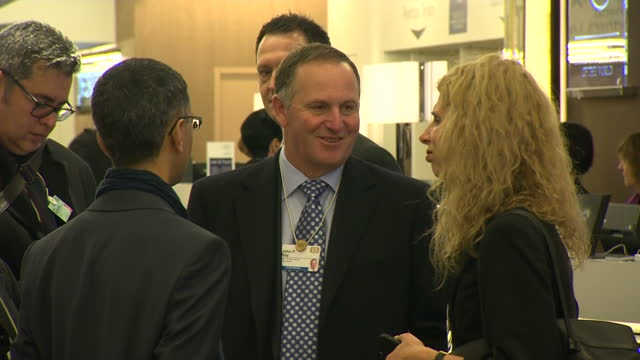 Shows interior lobby entrance to World Economic Forum event New Zealand PM John Key talking with associates on January 22 2015 in Davos Switzerland