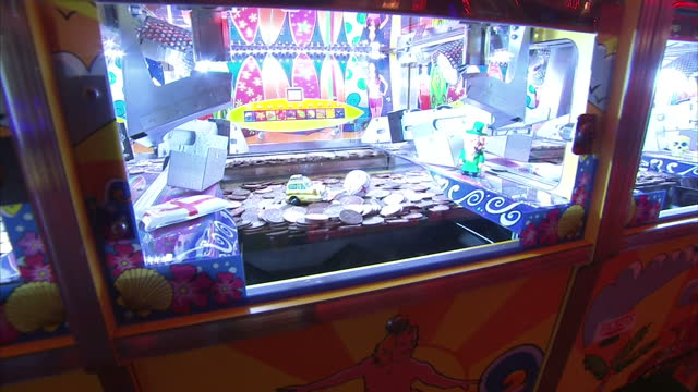 Shows Interior shots Amusement Arcade coin pusher machine with close ups of coins and toys in machine on November 10 2015 in London England