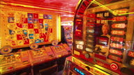 Shows Interior shots Amusement arcade games with lights flashing and sounds playing and close ups Deal or No Deal arcade game and 'No Deal' button...
