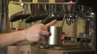 Shows interior shots barista in coffee shop warming or frothing milk in metal jug on 13th February 2017 in Alexandria Virginia United States