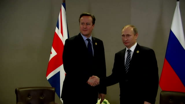 Shows Interior shots British Prime Minister David Cameron meeting Russian President Vladamir Putin shaking hands and sitting down talking David...