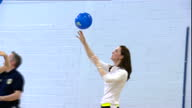 Shows interior shots Catherine Duchess of Cambridge taking part in tennis workshop doing training exercises with balloon performing drills with...