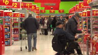 Shows interior shots price signs around Asda supermarket shoppers walking through aisles looking at goods on January 13 2015 in London England