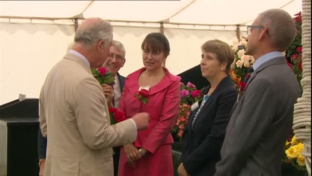 Shows interior shots Prince Charles Prince of Wales and Camilla Duchess of Cornwall walking into tent and meeting flower growers at Sandringham...