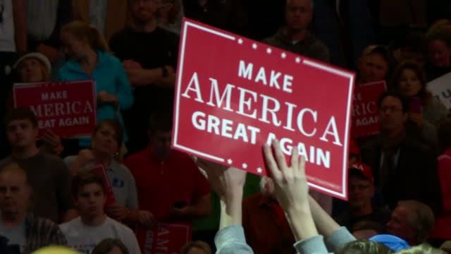 Shows interior shots Trump supporters standing listening waving signs and cheering as Donald Trump speaks at Than You Tour event Presidentelect...