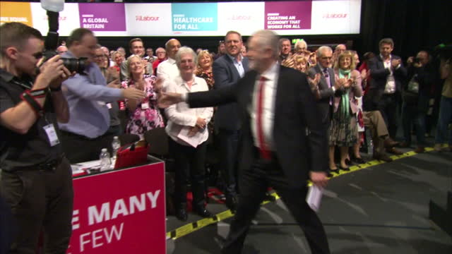 Shows interior shots UK Labour Party Leader Jeremy Corbyn arriving for his speech walking out and onto stage shaking hands with supporters and...