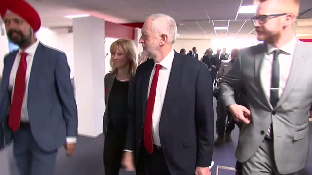 Shows interior shots UK Labour Party Leader Jeremy Corbyn walking into Conference venue with other Labour Officials and heading towards Conference...