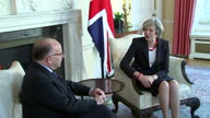 Shows interior shots UK Prime Minister Theresa May walking into room and sitting with French Prime Minister Bernard Cazaneuve and welcoming him to...