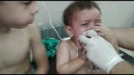 Shows interior shots young children looking distressed being treated in hospital with oxygen over alleged chlorine gas attack Dozens of people have...