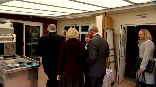 Shows Prince Charles and Camilla walking over bridge to get to Tea Pot island Royal couple chat with representatives and enter Teapot island museum...