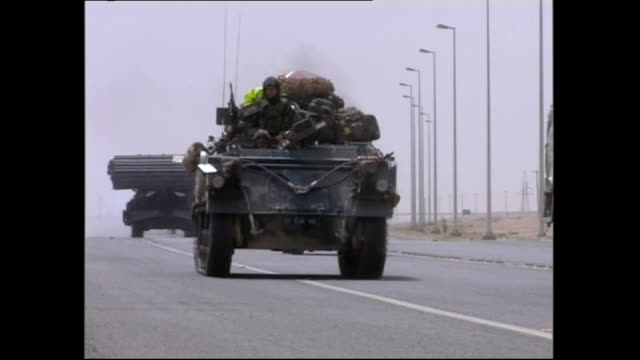 Shows US military convoy with heavy military vehicles including personnel carriers and tanks driving past on Baghdad road near Iraq / Kuwait border
