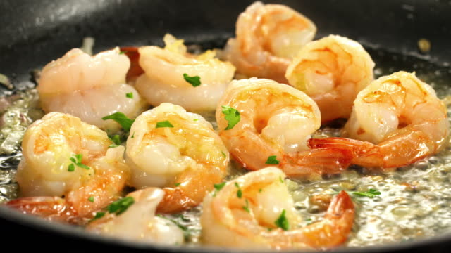 MS Shrimp scampi in skillet being sauteed in oil and parsley sprinkled on top / Los Angeles, California, United States