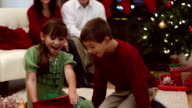 Siblings excitedly hug parents after opening present on Christmas morning