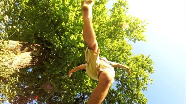 SLO MO Siblings jumping over the camera
