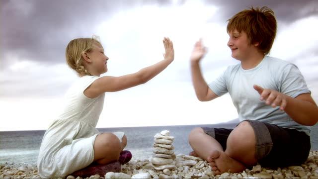 SLO MO Geschwister spielt mit Kieselsteinen auf den Strand