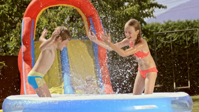 SLO MO Siblings splashing each other with water in an inflatable pool