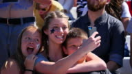 MS Siblings taking selfie with smartphone while sitting in stadium during football game