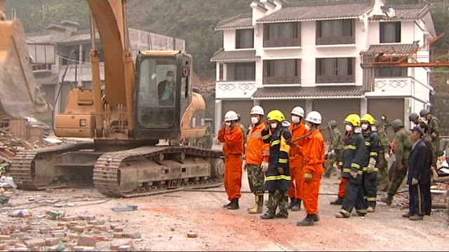 search for survivors in Hongbai Rescuer sitting in bulldozer as moved over rubble in search of survivors / Bulldozer clearing rubble from roof of...