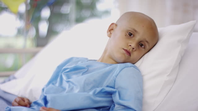 Sick little boy in hospital bed with cancer